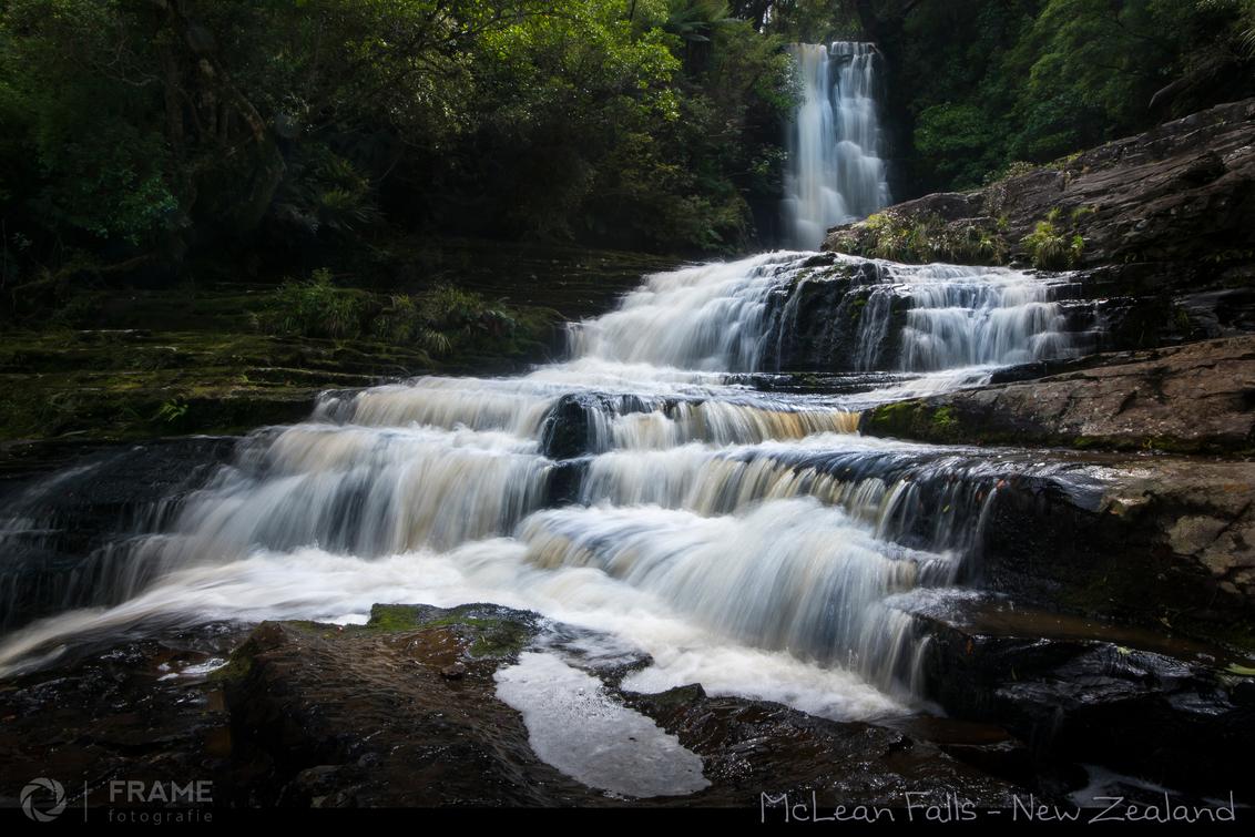 """McLean Falls - Niet veel toeristen doen de Catlins aan tijdens hun reis door het waanzinnig mooie Nieuw Zeeland, maar het verrassende """"teletubbie""""-achtige zuidooste - foto door framefotografie op 02-01-2019 - deze foto bevat: water, natuur, vakantie, reizen, landschap, waterval, rivier, watervallen, beek, reisfotografie, mclean, catlins, nieuw zeeland, mclean falls"""