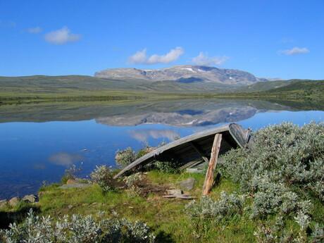 Oude boot en reflectie in Noors meer.