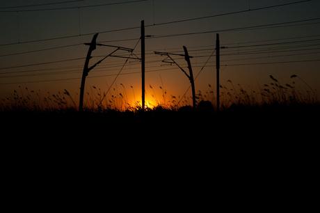Spoorlijn langs de A15 bij zonsondergang