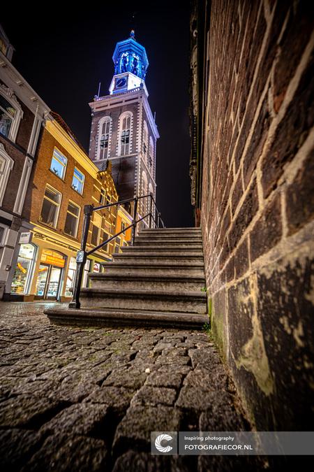 Kikvorsperspectief in Kampen - Vanuit een onmogelijke hoek en in een bizarre houding gevouwen lukte het me het lijnenspel samen te laten komen. De vertekening was nog een uitdaging - foto door Fotografiecor op 21-11-2020 - deze foto bevat: oud, foto, kleur, straat, licht, avond, architectuur, spiegeling, reflectie, schaduw, fotograaf, stad, nacht, light, compositie, huis, historisch, straatfotografie, overijssel, groothoek, centrum, painting, avondfotografie, hanzestad, Nieuwe Toren, oude stadhuis, lijnperspectief