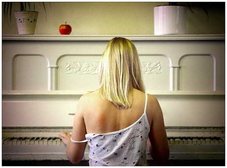 By the piano.