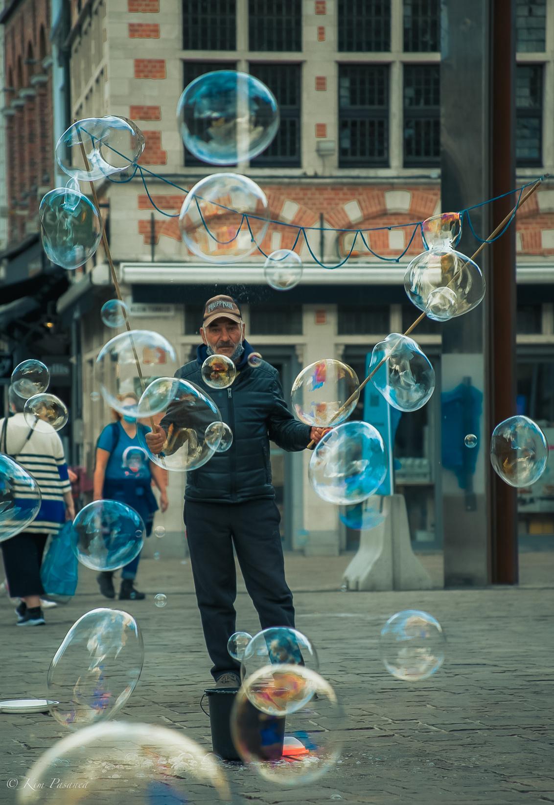 Bellenblazen - Tijdens een weekendje Gent zag ik deze man op een plein. Bellenblazen, wie heeft het nou niet gedaan in zijn/haar jeugd. Dit waren grotere bellen, ma - foto door kimudin op 08-09-2020 - deze foto bevat: bellen, gent, straatfotografie