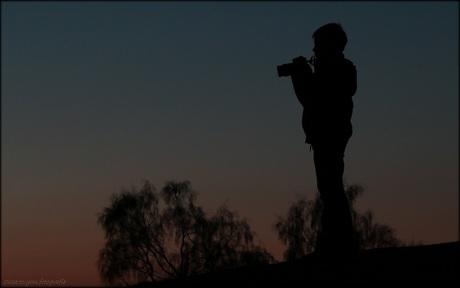 silhouette van een jonge fotograaf...