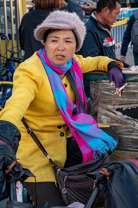 Straatverkoper in Beijing - Straatverkoper in Beijing - foto door robvdwo op 28-11-2018 - deze foto bevat: vrouw, mensen, china, straatfotografie, sigaret, beijing, reisfotografie, peking, 35mm