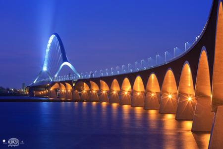 Een foto die ik in gedachten al gemaakt had - Sinds deze brug er is had ik al een foto in gedachten waarbij alle peilers in het wassende water van de Waal zouden staan. Nog steeds heb ik die foto - foto door nldazuu op 29-01-2018 - deze foto bevat: lucht, water, licht, avond, spiegeling, brug, rivier, avondfotografie, lange sluitertijd, blue hour, De Oversteek Nijmegen