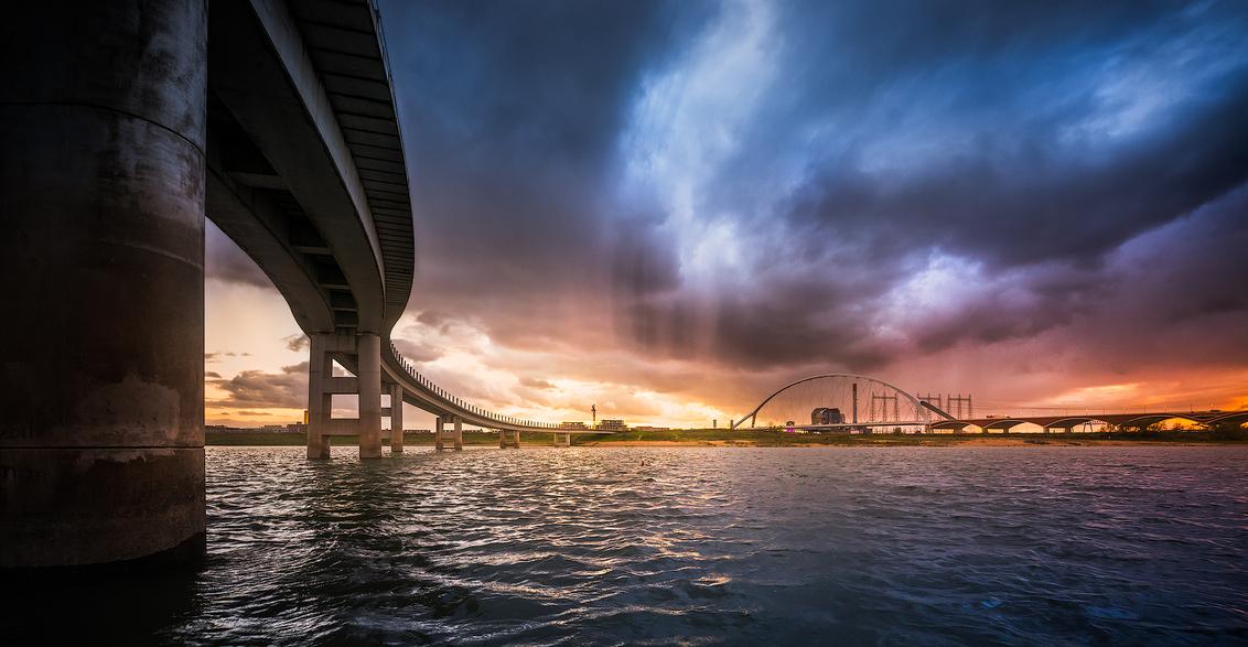 Zaligebrug - De Zaligebrug (zo heet dat ding nou eenmaal) en verderop de Oversteek bij Nijmegen. Met wat fantasie aangedikt maar het stormde en regende wel degel - foto door JLfoto op 07-03-2021 - deze foto bevat: lucht, wolken, water, natuur, herfst, avond, zonsondergang, architectuur, spiegeling, landschap, tegenlicht, storm, brug, rivier, nijmegen, polder, waal, oversteek, zaligebrug
