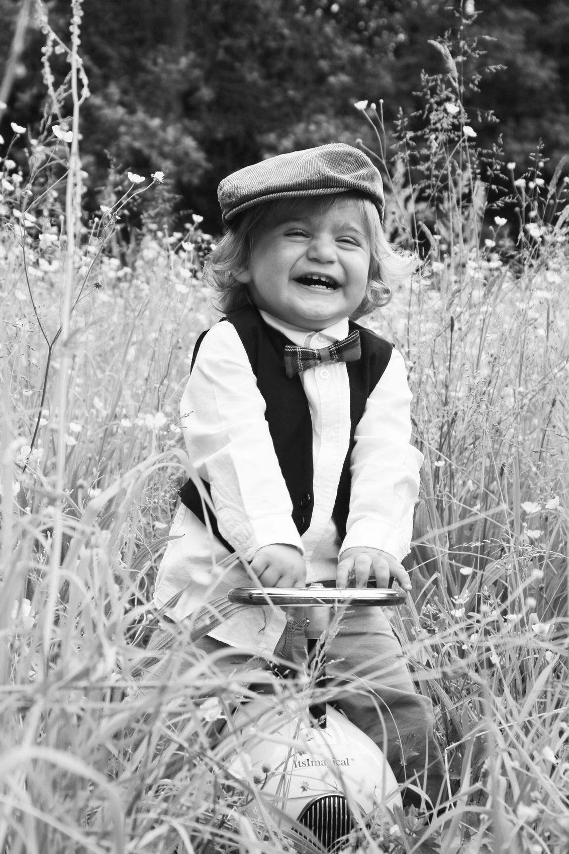 happy boy - broertje van Fay (vorige foto)  Kay op mijn loopfiets tussen de gele bloemen. - foto door APBFoto op 04-07-2014 - deze foto bevat: portret, kind, jongen, lief, beauty, zwartwit, loopfiets, bloemen veld