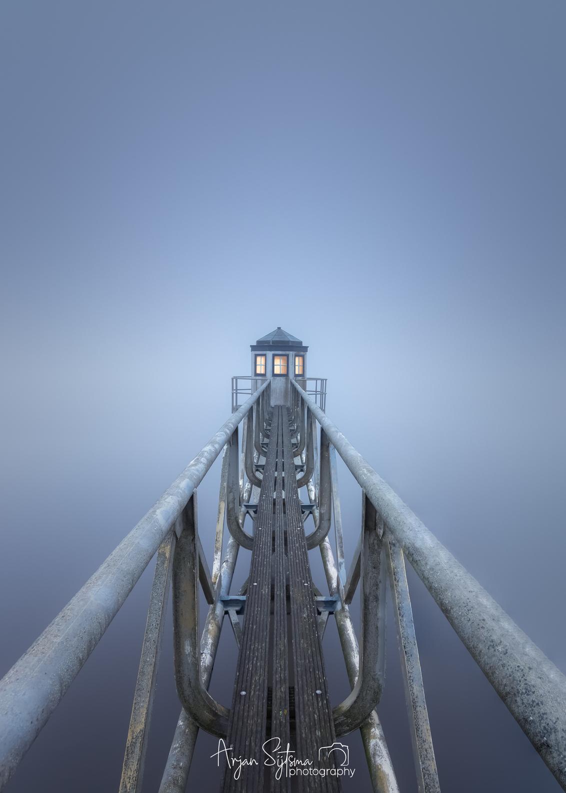 Minimalistisch Lauwersmeer - Op 27 februari '21 was het hier in het noorden een heel klein wereldje. Overal zat het potdicht door hardnekkige mist. Perfect weer om mooie minimali - foto door ArjanSijtsma op 25-03-2021 - deze foto bevat: lucht, wolken, blauw, zee, water, vuurtoren, natuur, licht, ochtend, winter, lijnen, landschap, mist, tegenlicht, zonsopkomst, meer, haven, brug, kust, dauw, lauwersmeer, grijs, friesland, ochtendlicht, diepte, lichtinval, oostmahorn, peilschaal, fryslan, minimalistisch, lange sluitertijd, long exposure, kleine wereld, dichte mist, potdicht