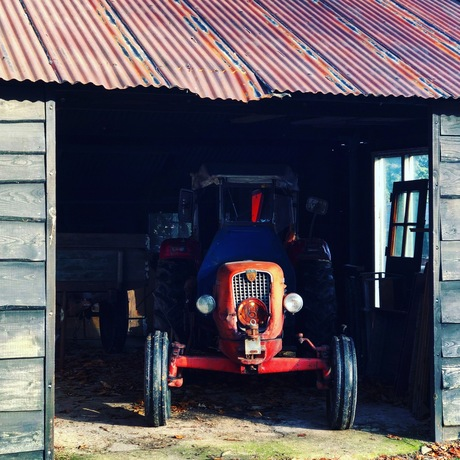 Oude tractor in loods