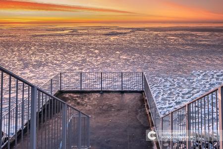 Winters uitzicht over het IJsselmeer - De winter van 2021 was kort en heftig maar de magie is tijdloos. Een blik op een bevroren landschap vanaf het monument op de afsluitdijk. De zonsopko - foto door Fotografiecor op 21-02-2021 - deze foto bevat: lucht, wolken, zon, strand, zee, water, dijk, panorama, natuur, licht, sneeuw, winter, avond, zonsondergang, ijs, spiegeling, landschap, tegenlicht, zonsopkomst, monument, meer, balkon, pier, brug, kust, nederland, horizon, groothoek, afsluitdijk, filter, nd, lange sluitertijd, benro