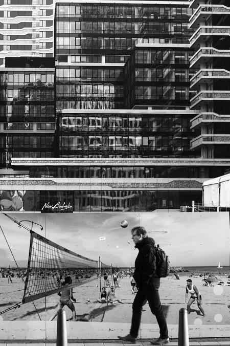 New Babylon - Strandbeelden verhullen de verbouwingen bij Den Haag CS. - foto door disone op 26-02-2020 - deze foto bevat: strand, lijnen, reclame, gebouw, stad, zwartwit, beach, wandelaar, babylon, Den Haag, New Babylon, voleyball