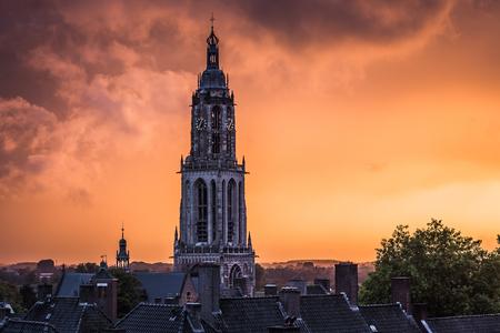 Tower of Power - Een krachtige lucht en een mooie oranje kleurende regenlucht. Een mooi contrast met de Cuneratoren van Rhenen. - foto door MaxterBurg op 02-10-2020 - deze foto bevat: lucht, wolken, zon, uitzicht, licht, oranje, herfst, avond, zonsondergang, landschap, mist, tegenlicht, kerk, storm, toren, kleurrijk, utrecht, rhenen, daken, herfstkleuren, charmant, regenwolken, authentiek, cuneratoren, cunerakerk, utrechtse heuvelrug