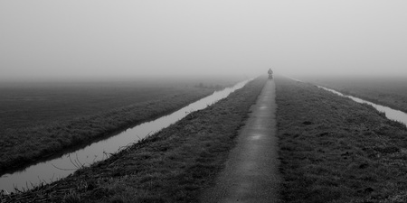 Op weg - In eenzaamheid door de mist naar het onbekende - foto door VincentvD op 05-01-2021 - deze foto bevat: fiets, mist, zwartwit, polder, straatfotografie, eenzaamheid