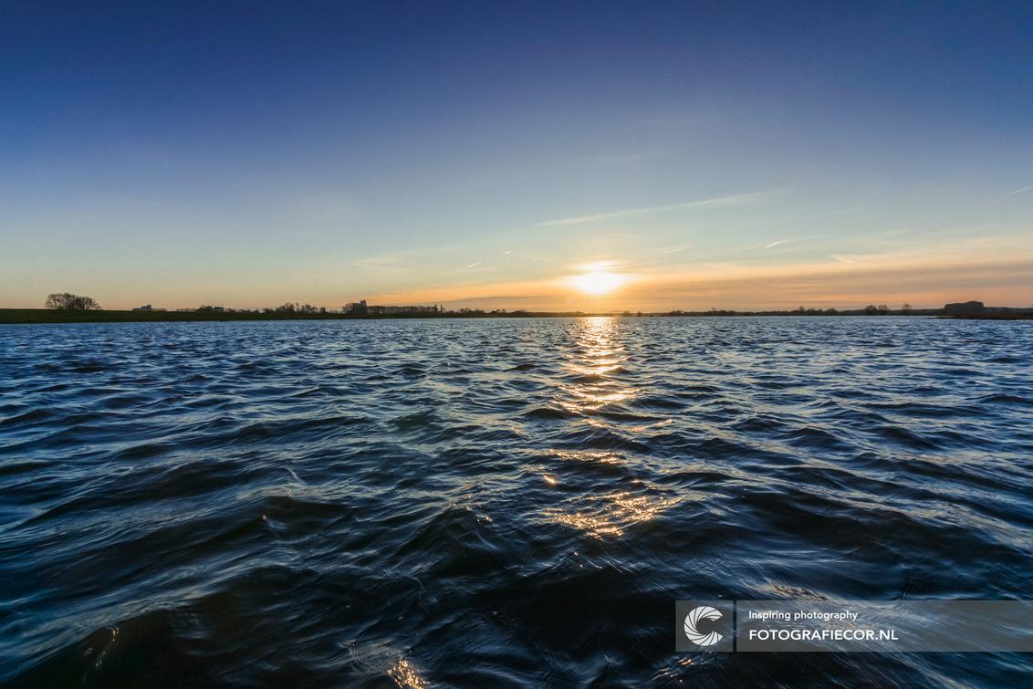 Zonsopkomst boven de uiterwaarden van de IJssel - Zonsopkomst boven de volgelopen uiterwaarden in het nationaal landschap de IJsseldelta. Een loopbrug over het water maakte deze foto mogelijk. De res - foto door Fotografiecor op 14-01-2018 - deze foto bevat: lucht, wolken, zon, water, panorama, natuur, licht, boot, winter, avond, zonsondergang, vakantie, spiegeling, landschap, tegenlicht, zonsopkomst, meer, golven, rivier, perspectief, polder, delta, horizon, stroming, golfslag, hoog water, Vreugderijkerwaard