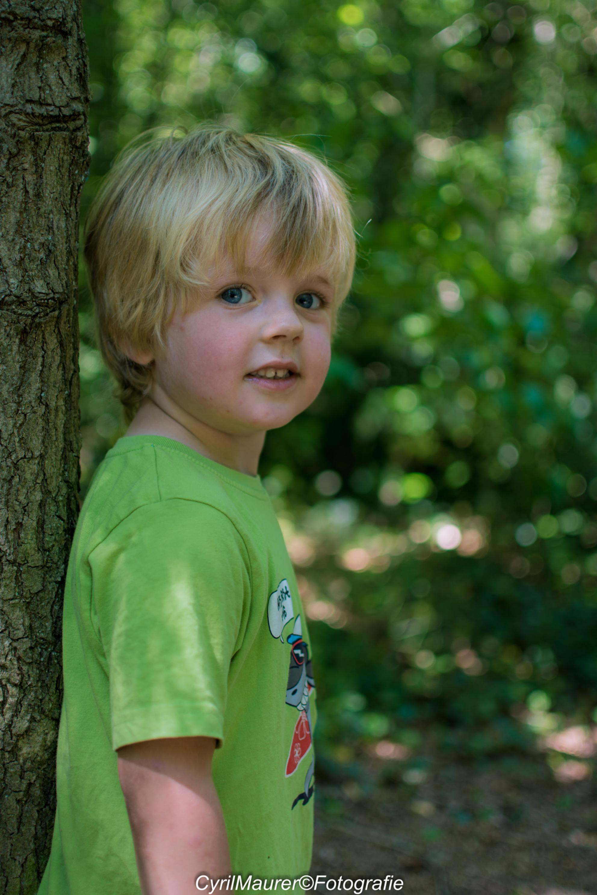 kijk papa nog een laatse foto nemen bij de boom - deze is genomen op de terug weg naar huis vlak bij de bos rand. ook hier was Lucas zelf an het poseren en was het een kwestie van lekker foto's,s sch - foto door sipmaurer op 20-07-2016 - deze foto bevat: groen, donker, bruin, portret, schaduw, daglicht, kind, ogen, lucas, buiten, blond, kleding, bokeh, 35mm, mijn zoon