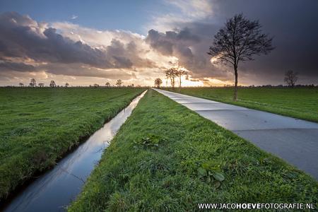 Dreigend - Genomen op 8 april 2014 in Rouveen. - foto door jacocanon op 08-04-2014 - deze foto bevat: zonsondergang, bomen, sloot, weerspiegeling, weg, dreigend, overijssel, beton, buien, april, rouveen, jacocanon