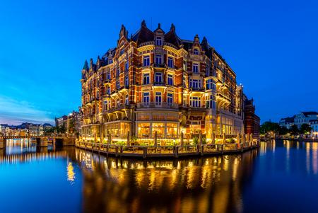 Hotel De L'Europe - De nacht treedt in bij Hotel De L'Europe in Amsterdam. Links nog een restje zonsondergang en rechts het blauwe uurtje. Omdat er nog geen rondvaartbot - foto door lbfoot op 03-06-2020 - deze foto bevat: amsterdam, avond, zonsondergang, amstel, verlichting, rokin, blauwe uur, lange sluitertijd, hotel de l'europe