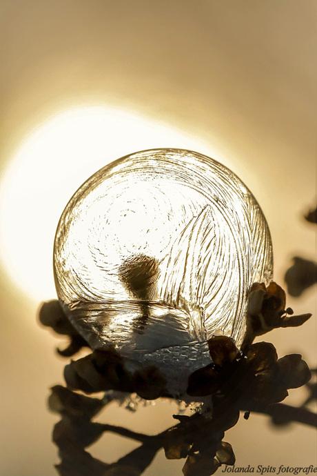 Bevroren zeepbel met de opkomende zon erachter