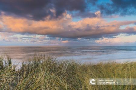 Daar aan de kust... - De wind raast je om de oren, de wolken drijven snel over je heen en de zee buldert erop los. Uitkijkend over het strand tussen het wuivende duingras  - foto door Fotografiecor op 27-02-2021 - deze foto bevat: lucht, wolken, zon, strand, zee, water, natuur, licht, zonsondergang, vakantie, landschap, duinen, zonsopkomst, storm, zand, kust, lange sluitertijd