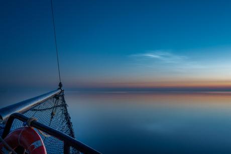 Lichtgevende nachtwolken op zee