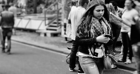 Tijdsbeeld - Gespot deze jongedame  op de Kermis in Dordrecht, zij gaat geheel op met  haar Smart Phone, dit mooie moment vastgelegd. - foto door f.arts1 op 12-04-2021 - locatie: Spuiboulevard, 3311 GR Dordrecht, Nederland - deze foto bevat: jeans, kapsel, fotograaf, wit, zwart, straatmode, brillen, zwart en wit, bagage en tassen, stijl