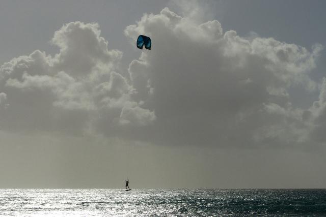 surfer springt een gat in de lucht - tegenlicht  - foto door Krea10 op 14-04-2021 - locatie: Aruba - deze foto bevat: wolk, water, lucht, atmosfeer, dag, vloeistof, cumulus, parachute, wind, horizon