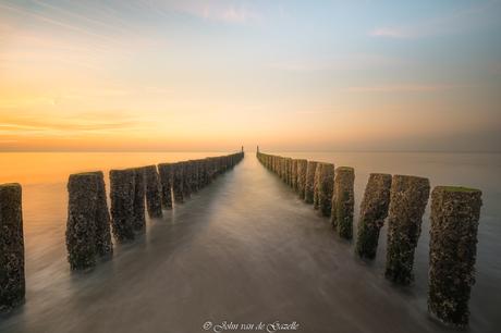 Golfbreker tijdens de zonsondergang op het strand van Domburg