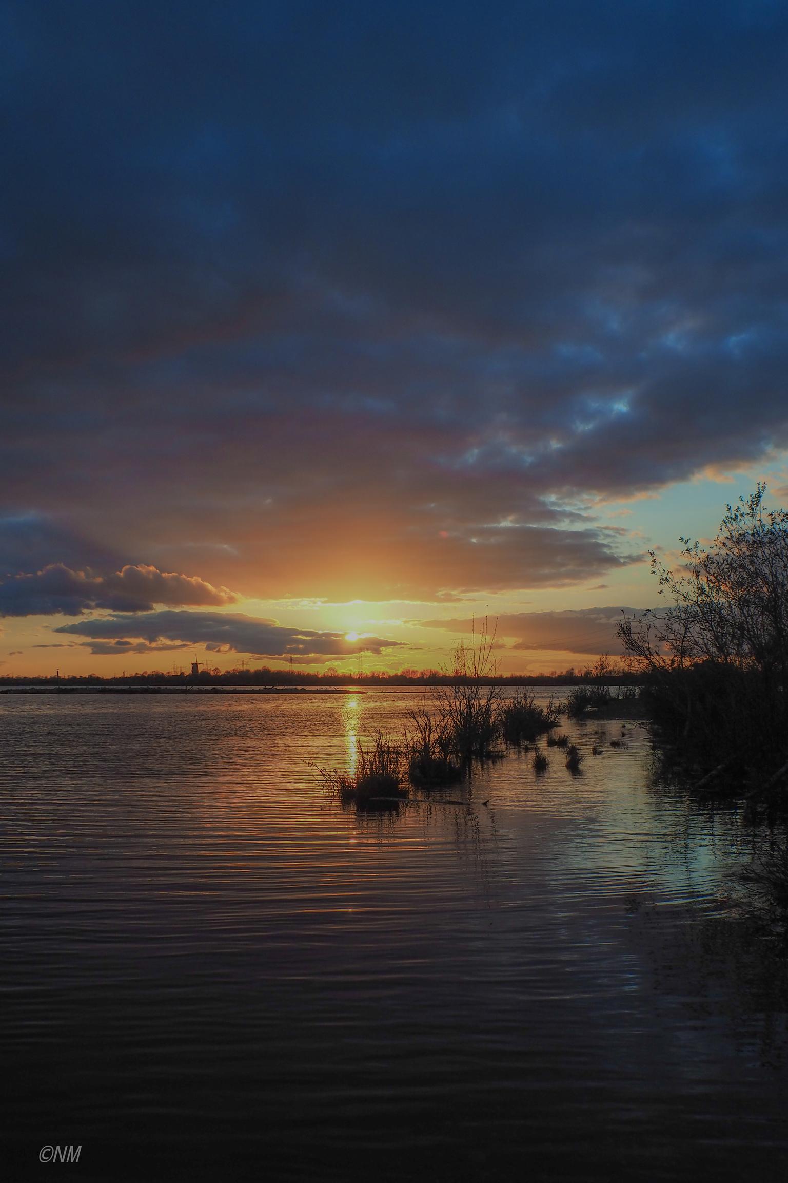 Zonsondergang - Mooie zonsondergang met donkere wolken - foto door Nancy72x op 16-04-2021 - locatie: 6051 Maasbracht, Nederland - deze foto bevat: wolk, water, lucht, nagloeien, natuurlijk landschap, meer, boom, rode lucht 's ochtends, bank, zonsondergang
