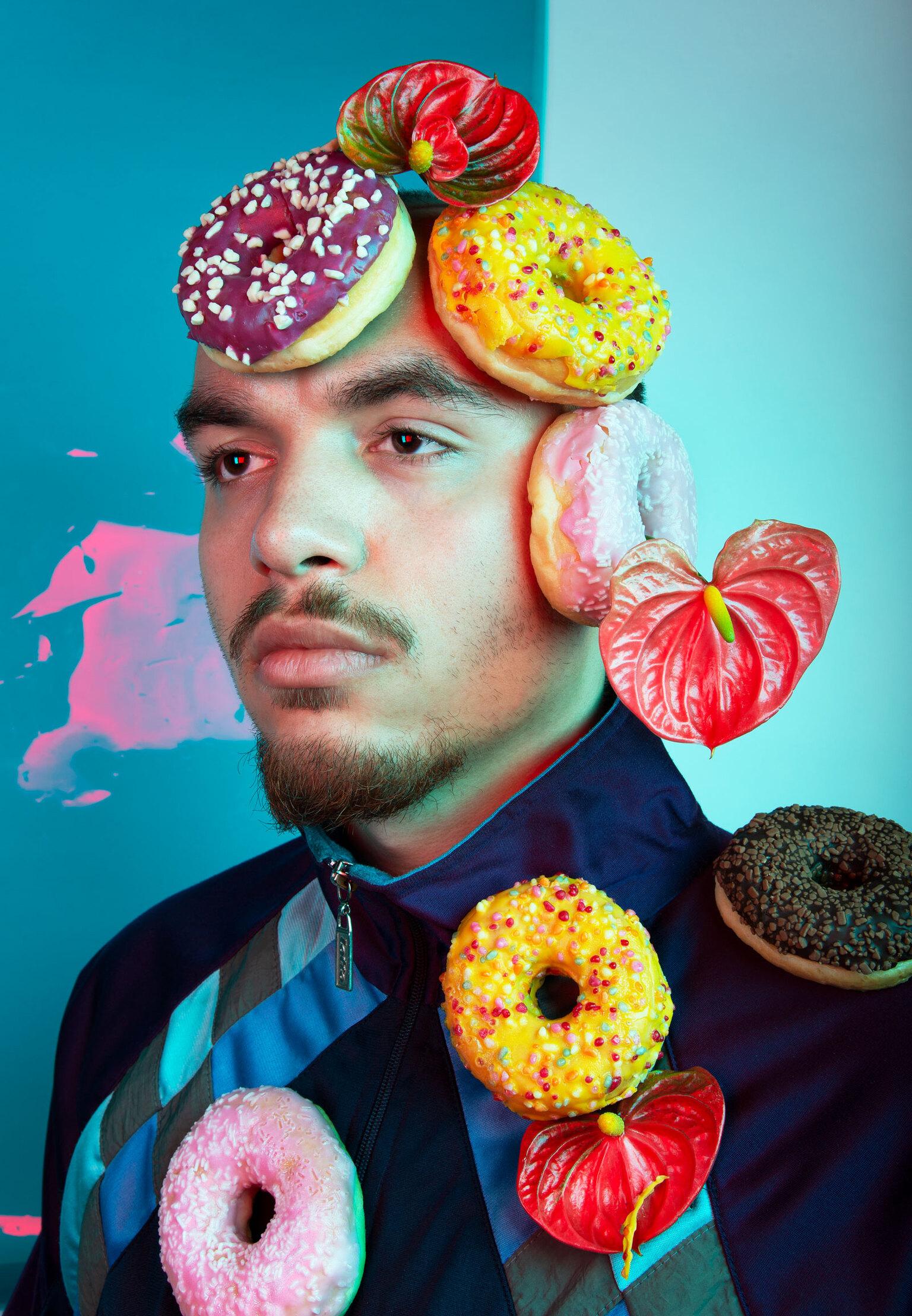 """Jermo - Donuts - Jermo is """"mijn favoriete huisgenoot"""". Als we elkaar op de gang tegenkomen is dit onze standaard groet. Jermo is een bijzonder mens. Hij heeft een fan - foto door SophieVermeulen op 14-04-2021 - deze foto bevat: donuts, portret, badmeester, kunst, fineartphotography, stillifeportrait, artist, foodart, gezicht, oog, hoofddeksel, bloem, gelukkig, fabriek, baard, evenement, kunst, zendspoel"""