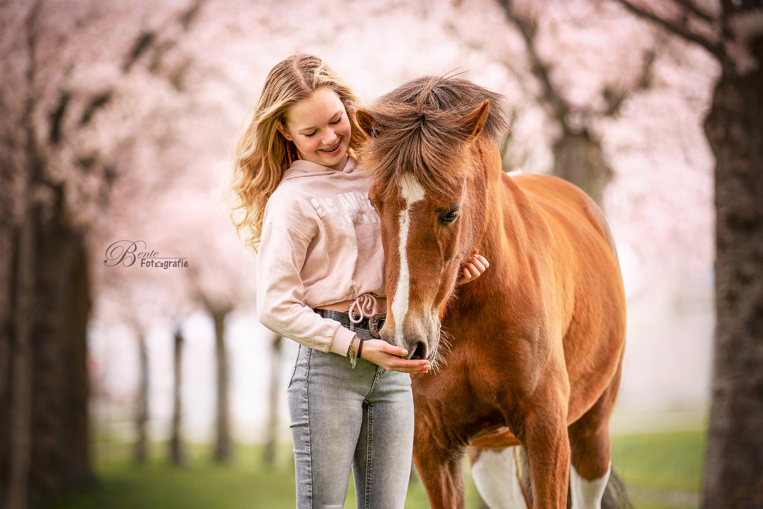 Mirte en Bonne - Mirte stond met haar pony Bonne model onder de bloeiende bloesembomen - foto door Bentefotografie op 12-04-2021 - deze foto bevat: paard, fabriek, jurk, mensen in de natuur, flitsfotografie, lever, gelukkig, werkend dier, gebaar, boom