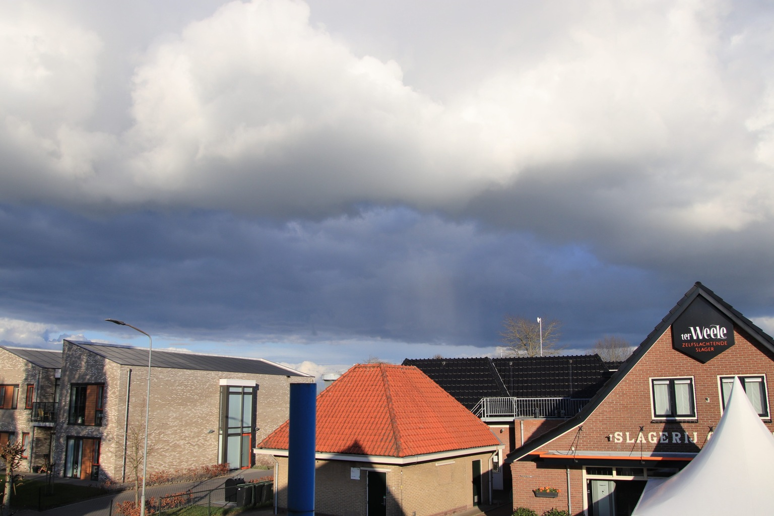 Donkere luchten - Donkere partijen lucht boven Oene - foto door ceos1000dthijs op 11-04-2021 - locatie: 8167 Oene, Nederland - deze foto bevat: wolk, lucht, gebouw, venster, huis, hout, cumulus, woongebied, landschap, stad