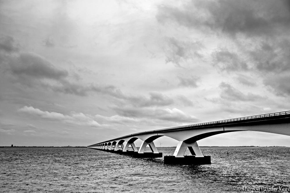 Walking over water - Zeelandbrug afgelopen zaterdag.  Iedereen hartelijk dank voor de waardering voor mijn werk. Lieve groeten,  Marjon - foto door MarjonvanderVegt1967 op 12-04-2021 - locatie: 5411 Zeeland, Nederland - deze foto bevat: zeeland, zeelandbrug, architectuur,, lucht, wolken, water, pijlers, land, zwart wit, wolk, water, lucht, zwart en wit, stijl, meer, balkbrug, horizon, cumulus, waterscooters