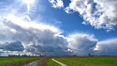 Winterse bui. - in april in noord Groningen. - foto door Aiso op 15-04-2021 - locatie: 9981 Uithuizen, Nederland - deze foto bevat: wolk, lucht, fabriek, atmosfeer, ecoregio, licht, natuurlijke omgeving, natuurlijk landschap, zonlicht, boom