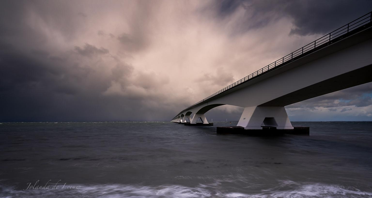 Zeelandbrug  - Bij de Zeelandbrug is het eigenlijk altijd mooi. Ook zo op deze onstuimige dag met felle buien  - foto door JolandadeLeeuw op 15-04-2021 - locatie: 4675 RB Nederland - deze foto bevat: zeelandbrug, wolken, water, zeeland, brug, buien, oosterschelde, wolk, water, lucht, meer, horizon, kalmte, vloeistof, balkbrug, stad, monochrome fotografie