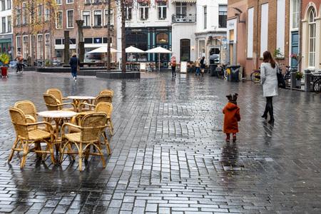 Regen in coronatijd - Moeder en dochter aan de wandel - foto door viterson op 10-04-2021 - locatie: Zaadmarkt, 7201 Zutphen, Nederland - deze foto bevat: water, dag, venster, weg oppervlak, infrastructuur, mens, vloeren, stoel, stedelijk ontwerp, weg