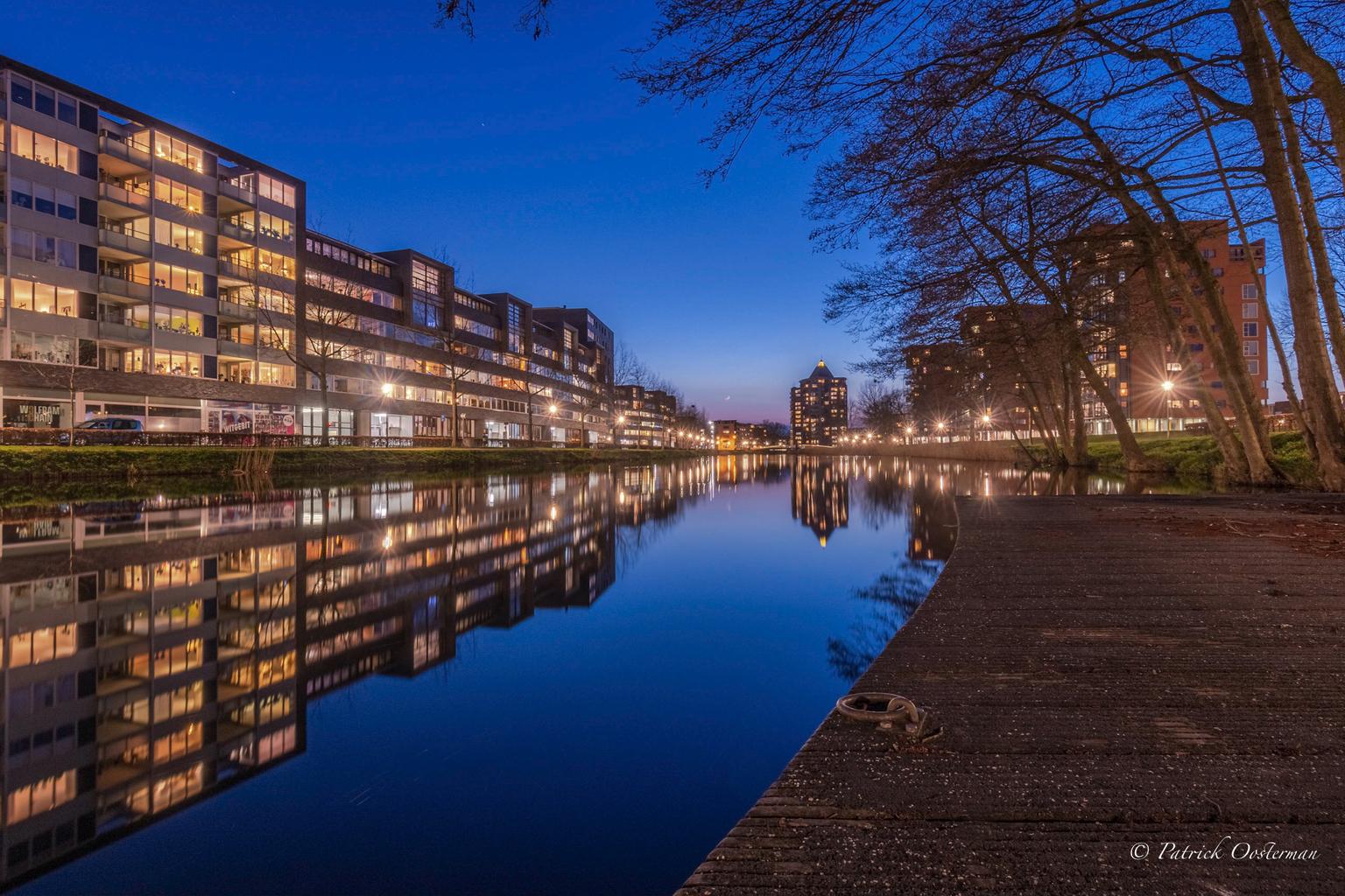 'T Apeldoornskanaal  - Het apeldoorns kanaal tijdens windstil blauw uurtje  - foto door Patrickoosterman op 14-04-2021 - locatie: Apeldoorn, Nederland - deze foto bevat: water, gebouw, lucht, fabriek, natuur, boom, schemer, zonlicht, stadsgezicht, waterloop