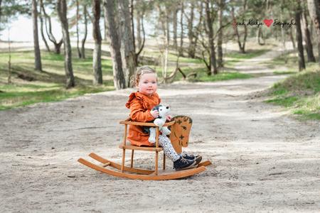 Hop paardje hop! - Een schattig meisje die 2 is en ook heel goed kan wegrennen. Ideaal met deze leeftijd is het om dan iets mee te nemen naar de shoot waar ze heel even - foto door l.a.nijboer op 13-04-2021 - locatie: Harderwijk, Nederland - deze foto bevat: kind, kinderen, meisje, lief, bos, daglicht, paard, kinderfotografie, fabriek, jurk, been, mensen in de natuur, boom, blad, hout, baby, gras, kinderwagen