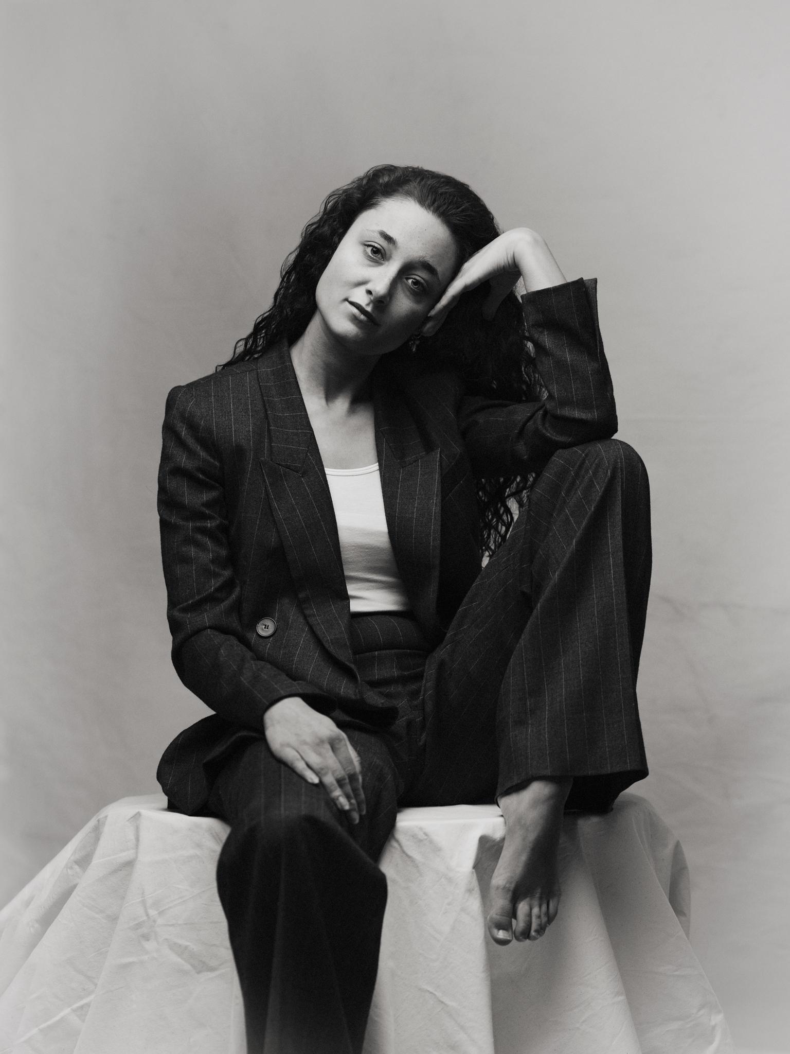 D E M I - * - foto door Marcel-Mellema op 13-04-2021 - deze foto bevat: portret, emotie, studio, vrouw, ogen, zwartwit, monochrome, flitsfotografie, mouw, straatmode, zwart en wit, zwart haar, mode ontwerp, knie, comfort, dij, jas