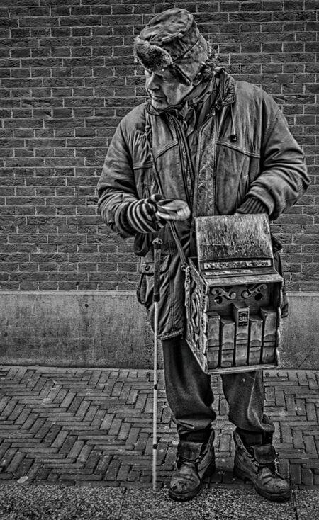 """wijlen Blinde Bennie Volkens - groot zien aub  in 2017 overleden na """"de Ziekte"""" ging  als kleine jongen met zijn vader al mee. Heeft nooit een uitkering aangevraagd.  Kwam en ging  - foto door c.buitendijk53 op 16-04-2021 - deze foto bevat: straatmuzikant,, blinde bennie, straat, straatfotogr, bovenkleding, fotograaf, wit, mens, zwart, zwart en wit, staand, stijl, openbare ruimte, musicus"""