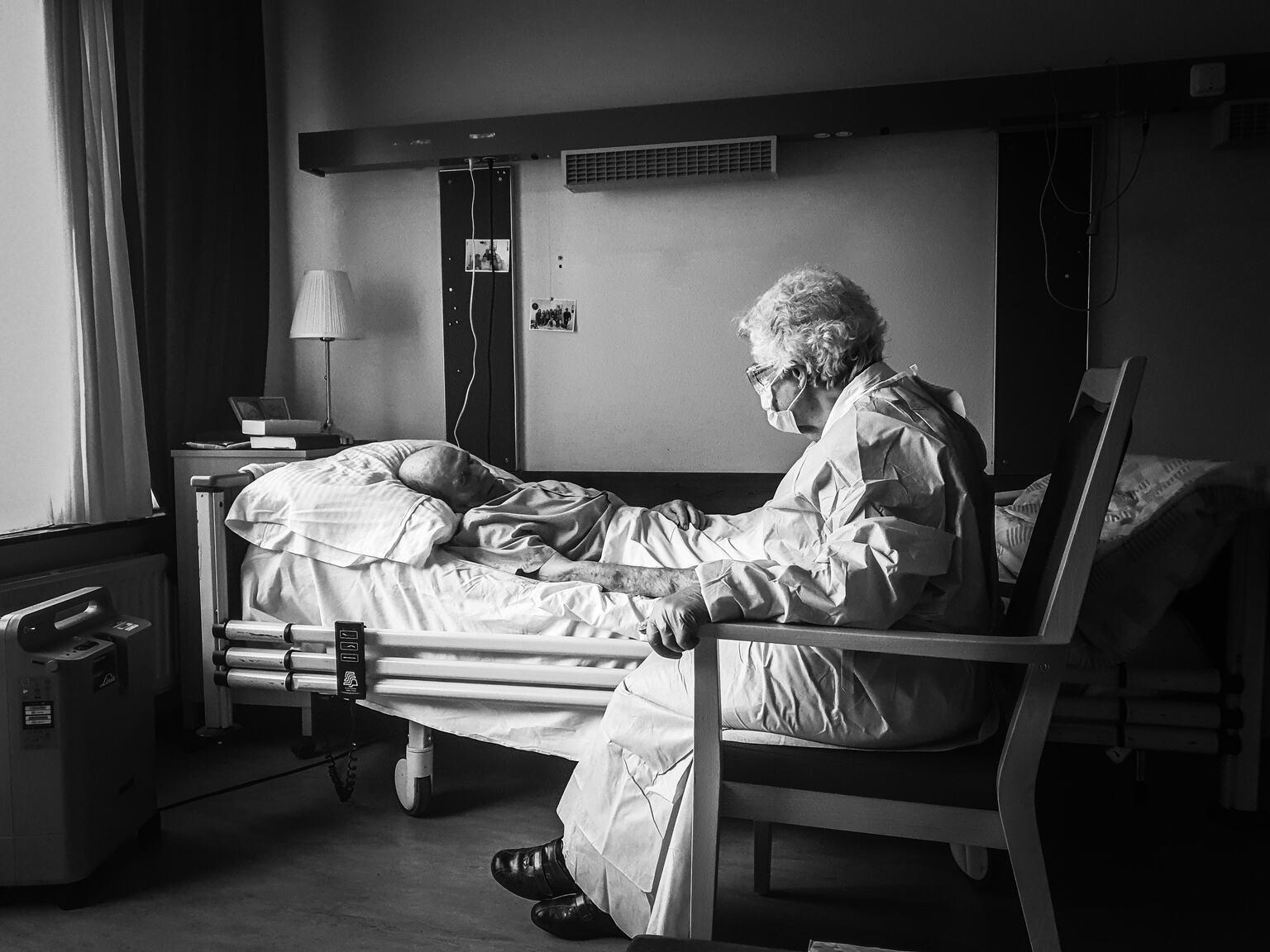 Pandemie-afscheid - Op deze foto staan 2 mensen die belangrijk voor mij zijn. Mijn stiefopa en mijn oma.  Mijn stiefopa woonde in een verzorgingshuis en heeft daar coron - foto door Brittk28 op 04-05-2021 - deze foto bevat: meubilair, comfort, zwart en wit, flitsfotografie, stijl, gordijn, monochroom, monochrome fotografie, tinten en schakeringen, fotolijst