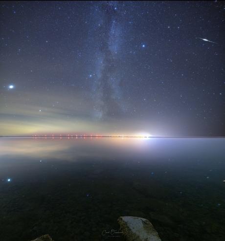 Melkweg reflectie en flarende sateliet.