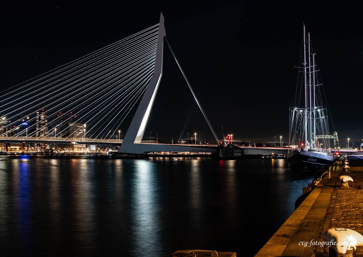 Nachtfotografie - Nachtfoto van de Erasmusbrug ook wel de zwaan genoemd en met aan de kade het zeilschip de eendracht. - foto door Cle59 op 14-04-2021 - locatie: Rotterdam, Nederland - deze foto bevat: water, lucht, licht, meer, lichaam van water, brug, gebouw, boot, stadsgezicht, tuibrug