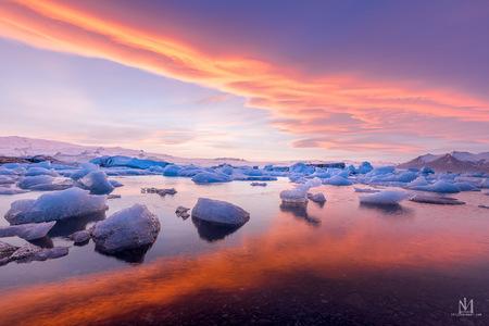 Jökulsarlón, IJsland - De gletsjer lagoon vanwaaruit de ijsschotsen de zee in stromen en terug op het strand van het beroemde Diamond Beach geworpen worden.  - foto door Thijsvermeer op 05-05-2021 - locatie: Jökulsárlón, IJsland - deze foto bevat: zonsondergang, wolken, ijs, ijsschotsen, reflectie, kleurcontrast, water, weerspiegeling, gletsjer, lagoon, wolk, water, lucht, atmosfeer, watervoorraden, natuurlijk landschap, schemer, meer, nagloeien, horizon